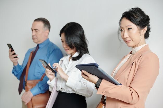 Skeptisch unzufriedene junge geschäftsfrau, die mit tablet-computer in den händen in der warteschlange steht