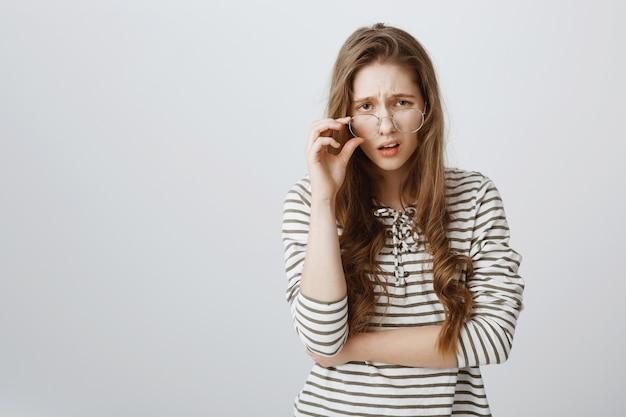 Skeptische frau in gläsern, die mit gleichgültigkeit schauen
