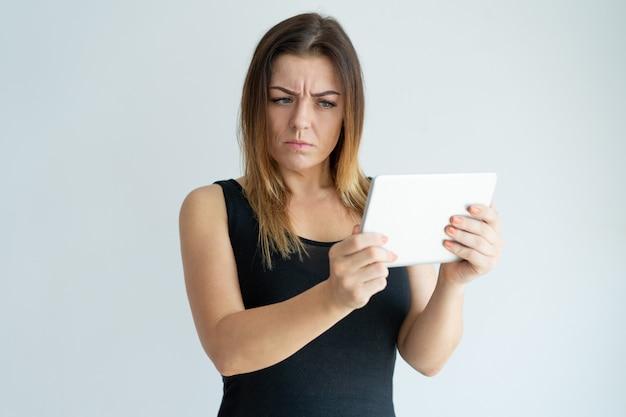 Skeptische hübsche frau, die nachrichten auf tablet-computer liest. dame, die auf tablette grast.