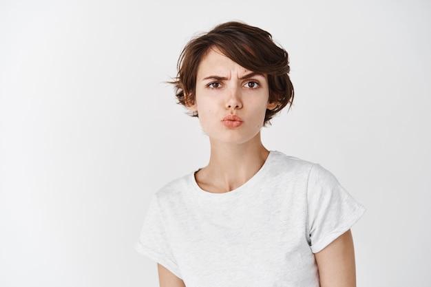 Skeptische kaukasische frau sieht verwirrt aus, verzieht die lippen und hebt die augenbrauen misstrauisch, fühlt sich zweifelhaft oder unsicher und steht auf weißer wand