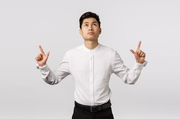 Skeptischer asiatischer geschäftsmann mag nicht, was er sieht, zögernd und verblüfft stehend, die stirn runzelnd und das schmollen gestört und oben schauen dem schrecklichen ergebnis zeigend und werfen unzufrieden auf