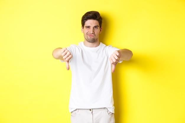 Skeptischer typ, der daumen nach unten zeigt und grinst, nicht mag und nicht zustimmt, auf gelbem hintergrund steht