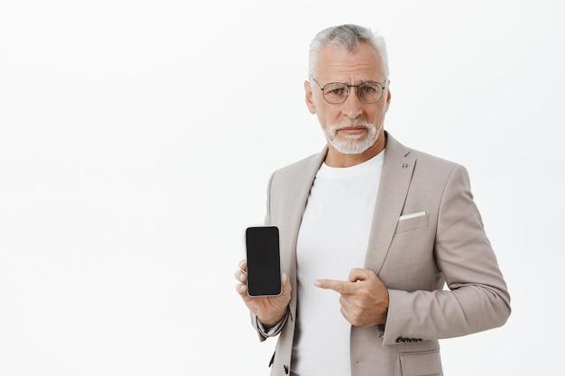 Skeptischer und nicht amüsierter alter geschäftsmann, der finger auf smartphone mit widerstrebendem ausdruck zeigt