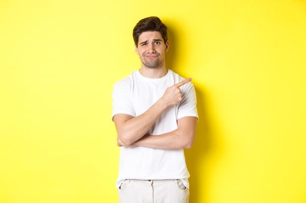 Skeptischer und unbeschwerter mann, der mit dem finger direkt auf etwas lahmes zeigt, widerstrebend die stirn runzelt und über gelbem hintergrund steht.