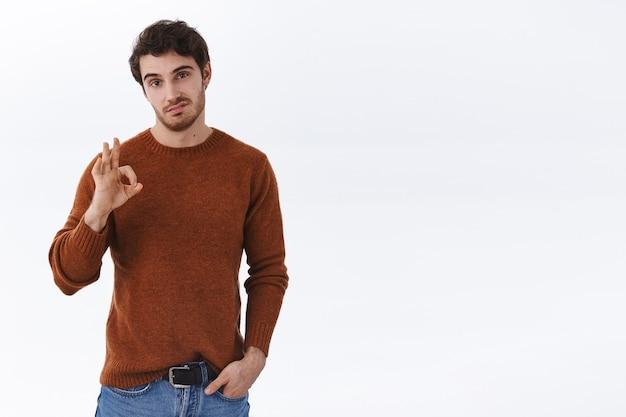 Skeptischer und wählerischer junger gutaussehender mann bewerten durchschnittliches produkt