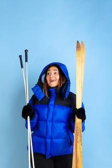 Ski-liebhaber. porträt der kaukasischen frau auf blauem studio