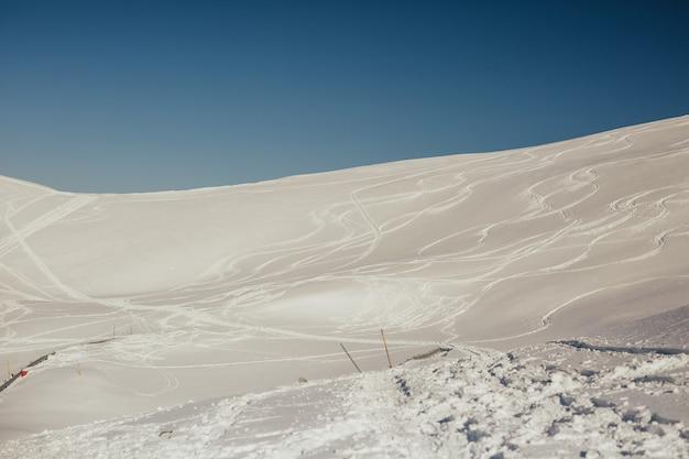 Ski- und snowboardwege und -spuren auf schnee und blauem himmel auf hintergrund.