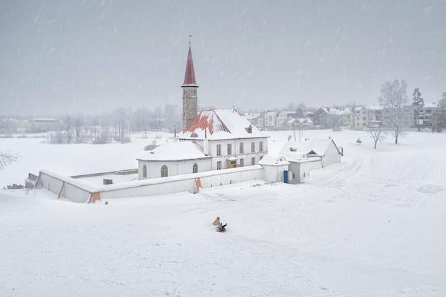 Skifahren mit rutschen im winter. weiße schneelandschaft mit altem maltesischem palast in der schönen natürlichen landschaft. gatchina. russland.
