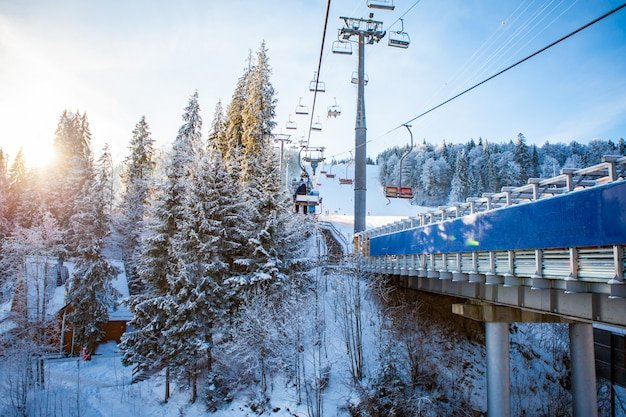 Skifahrer auf dem skilift fahren im skigebiet mit wunderschönen wäldern