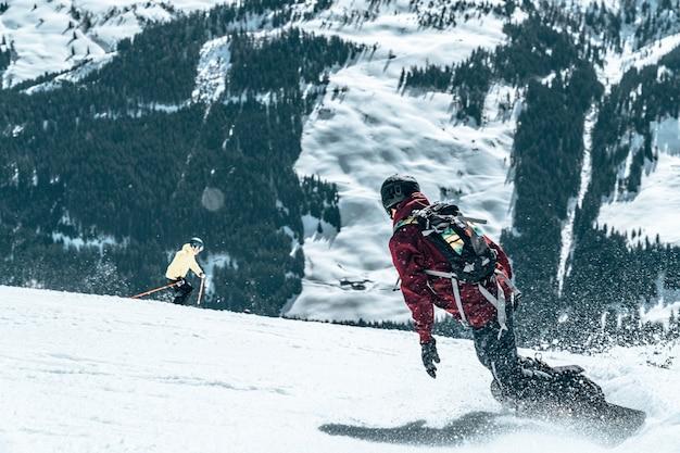 Skifahrer beim skifahren auf einem verschneiten berg bei tageslicht