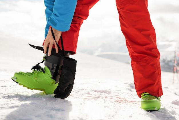Skifahrer bindet seinen stiefelriemen