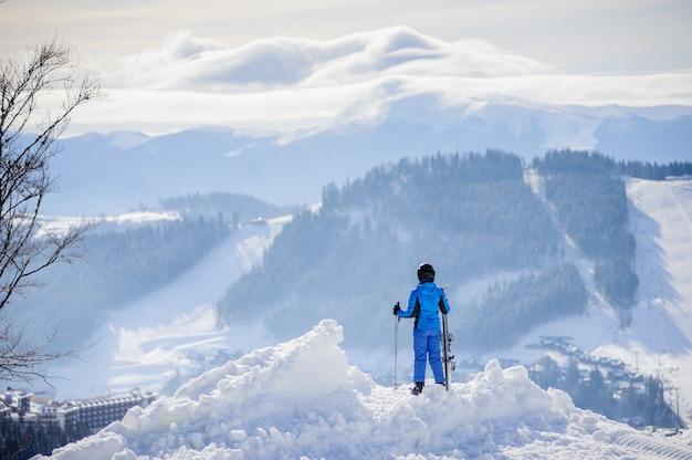 Skifahrer, der die ansicht über winterberge an einem sonnigen tag genießt