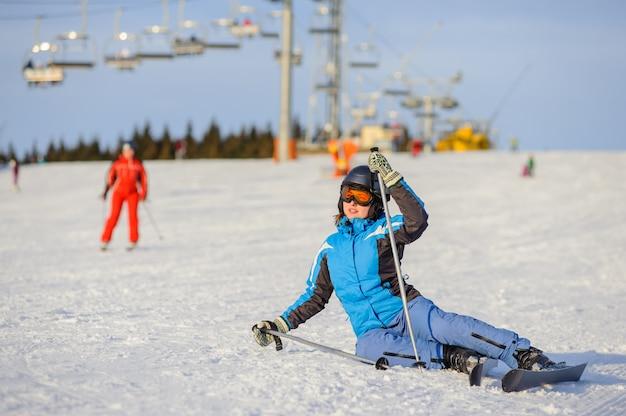 Skifahrer der jungen frau nach dem fall auf berghang