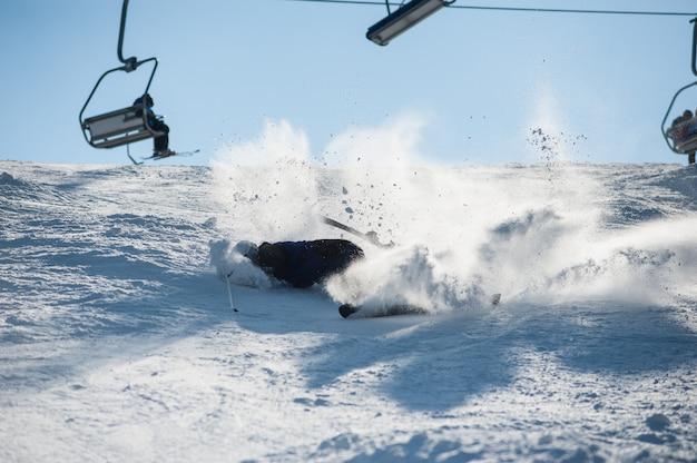 Skifahrer, der mit neuschneepulver auf der steigung fällt