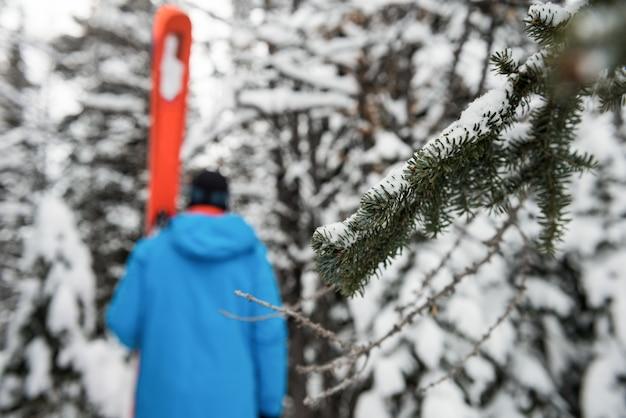 Skifahrer, der mit ski auf schneebedeckten bergen geht