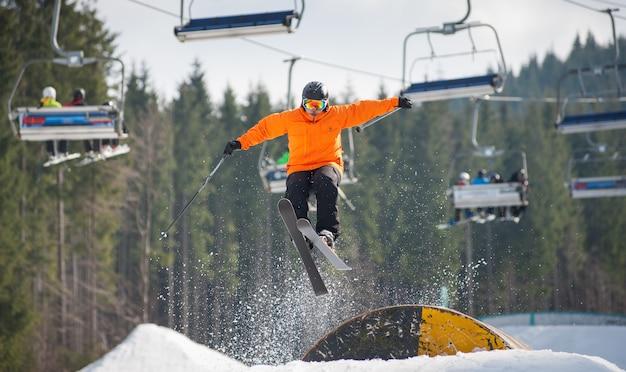 Skifahrer, der über eine hürde am wintertag fliegt