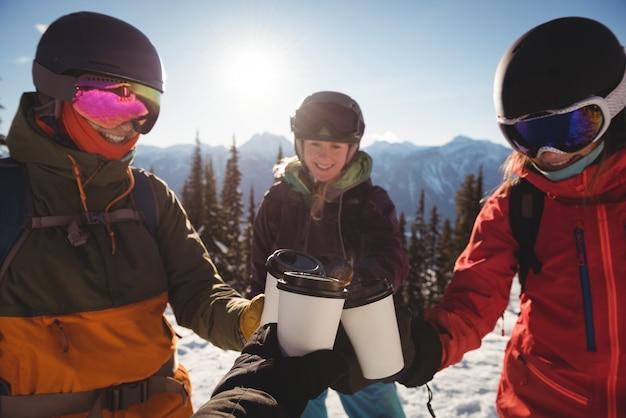 Skifahrer, die eine tasse kaffee auf einem schneebedeckten berg rösten