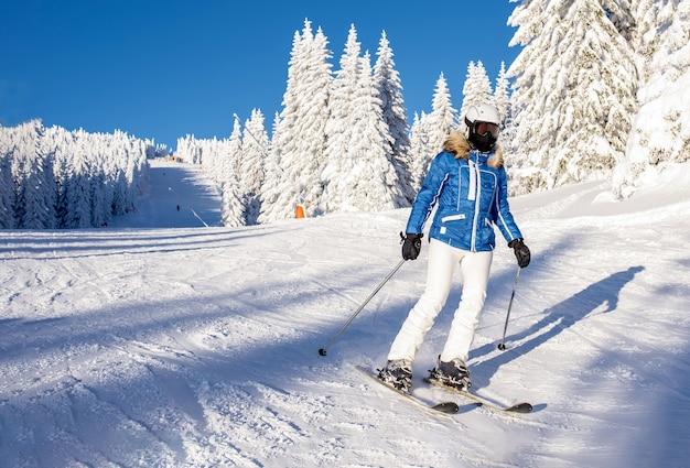 Skifahrer, die im bergresort den hügel hinunterfahren