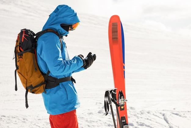Skifahrer mit handy auf den schneebedeckten bergen