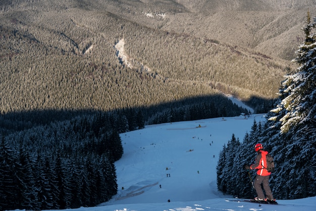 Skifahrer mit rucksack stehen ganz oben auf der abfahrt und bereiten sich auf das skifahren vor