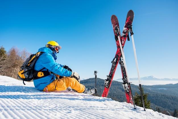 Skifahrer sitzen am hang in der nähe seiner skiausrüstung und genießen es