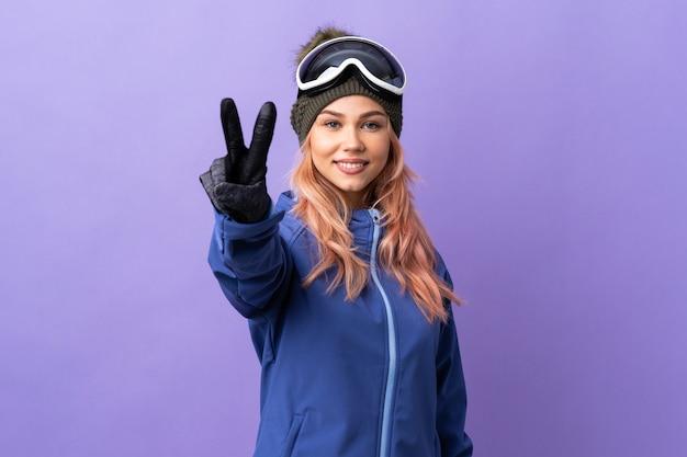 Skifahrer-teenager-mädchen mit snowboardbrille über isolierter lila wand lächelnd und siegeszeichen zeigend