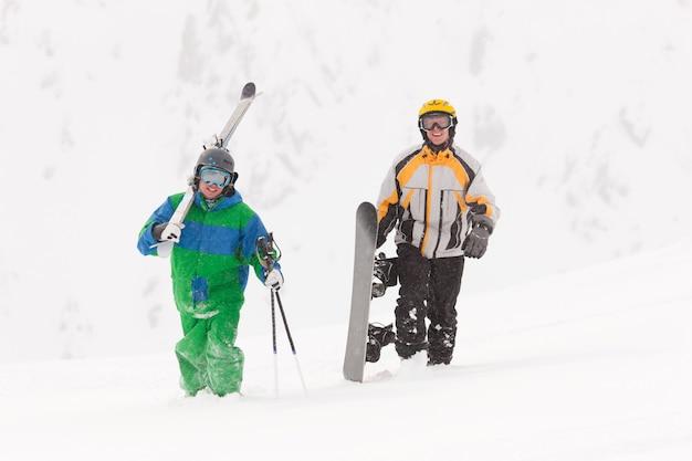 Skifahrer und snowboarder tragen ausrüstung