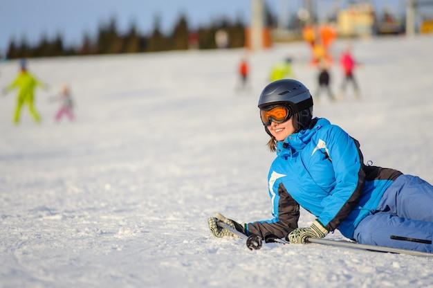 Skifahrerfrau, die auf dem schnee am skiort an einem sonnigen tag liegt