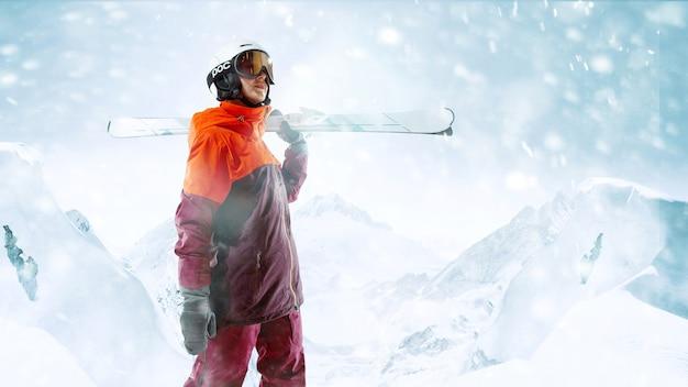Skifahrerin, die mit himmeln in einer hand auf schönem berglandschaftshintergrund steht. winter, ski, schnee, urlaub, sport, freizeit, lifestyle-konzept
