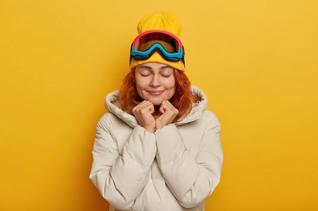 Skifahrerin genießt freizeit, hält hände unter dem kinn, augen geschlossen, mag wintersport, trägt hut und weißen kittel, schützende snowboardmaske, isoliert über gelber wand