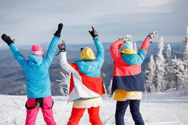 Skifahrerinnen, snowboarderinnen freuen sich am berghang. mehrfarbige, helle ausrüstung, hände erhoben. rückansicht. gesunder lebensstil. sportkonzept. selektiver fokus.