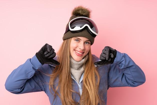 Skifahrerjugendlichmädchen mit dem snowboardingglashintergrund stolz und selbstzufrieden