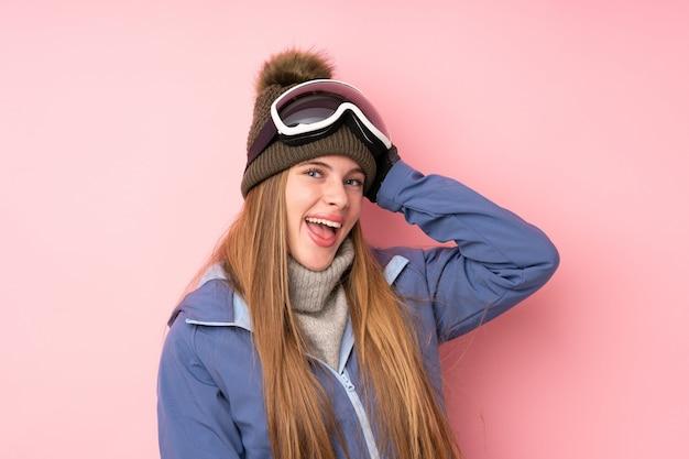 Skifahrerjugendlichmädchen mit snowboardinggläsern über getrenntem rosafarbenem lachen