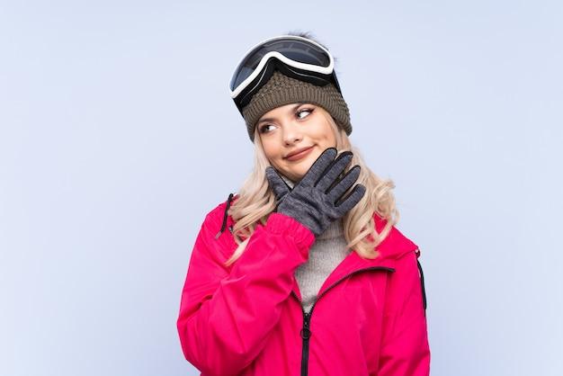 Skifahrerjugendlichmädchen mit snowboardinggläsern über lokalisiertem blau eine idee denkend