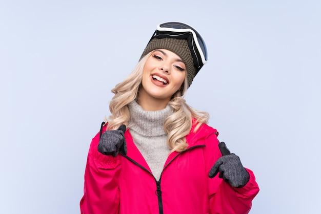 Skifahrerjugendlichmädchen mit snowboardinggläsern über lokalisiertem blau stolz und selbstzufrieden