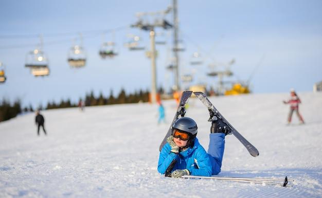 Skifahrermädchen, das auf dem schnee an einem sonnigen tag gegen skilift am skiort liegt