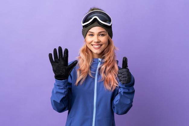 Skifahrermädchen mit snowboardbrille auf isoliertem purpur, das sechs mit den fingern zählt