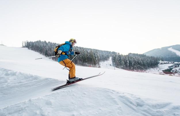 Skifahrermann am sprung von der steigung von bergen