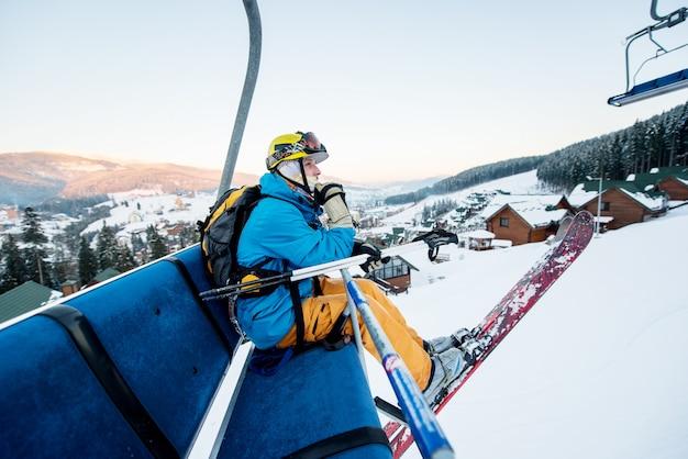 Skifahrermann, der am skisessellift am schönen tag sitzt