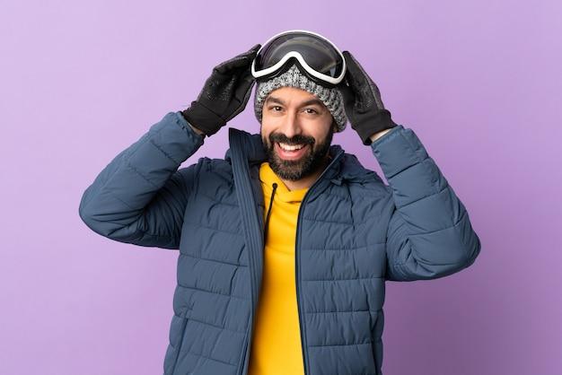 Skifahrermann mit snowboardbrille über isolierter lila wand