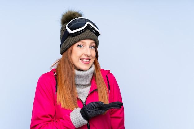 Skifahrerrothaarigefrau mit snowboardinggläsern über ausdehnungshänden der lokalisierten blauen wand zur seite, damit die einladung kommt