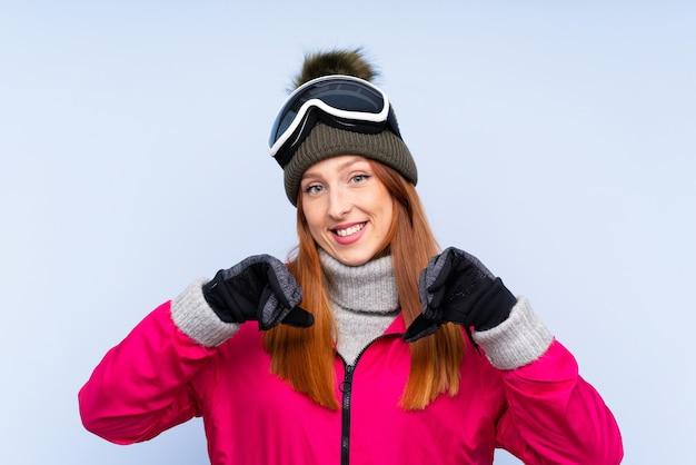 Skifahrerrothaarigefrau mit snowboardinggläsern über lokalisierter blauer wand stolz und selbstzufrieden