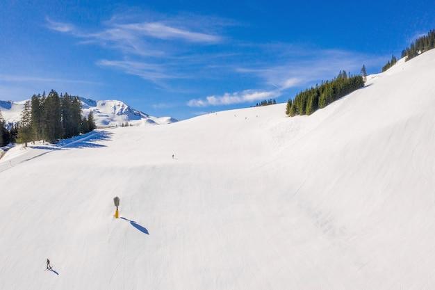 Skigebiet mit skifahrern, die unter einem blauen himmel den schneebedeckten hang hinunterrutschen