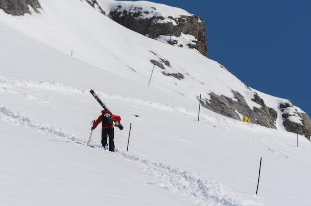 Skipatrouille klettert auf einen berghang mit großen skiern