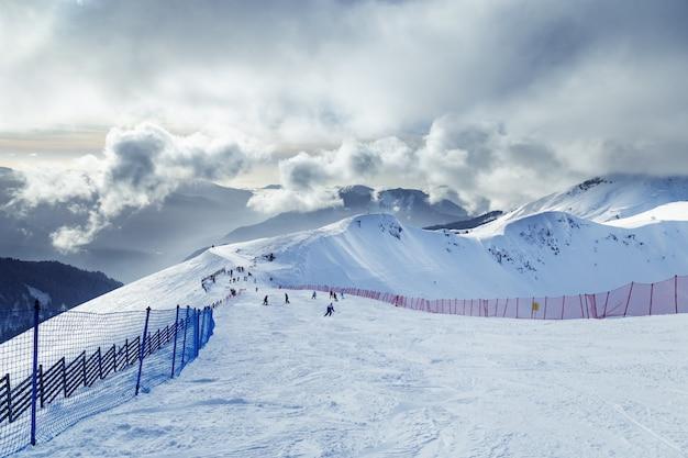 Skipiste, berggipfel, blauer himmel mit wolken, kaltes wetter. winterlandschaft. schöne aussicht auf das skigebiet krasnaya polyana in der russischen föderation.