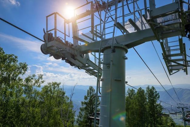 Skisesselliftturm auf dem hintergrund des blauen himmels mit weißen wolken und grünem gebirgstal im sonnigen sommertag.