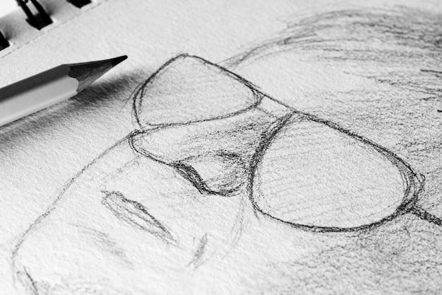 Skizze in einem notizbuch: bleistiftzeichnung eines männlichen gesichts mit brille.