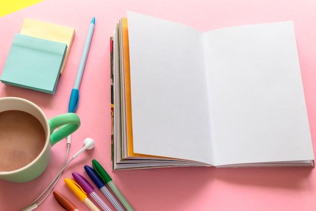 Skizzenblock (notizbuch), mehrfarbige stifte, tasse mit kaffee und kopfhörer auf rosa hintergrund
