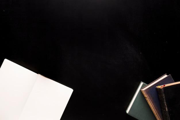 Skizzenblock und bücher auf schwarzem schreibtisch