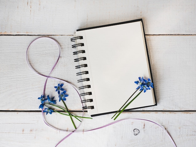 Skizzenbuch, leere seite, helle blume und rosafarbenes farbband